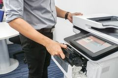 Businessman in grey shirt put ink toner cartridge into office multifunction printer for printing documents royalty free stock image