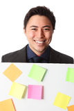 Businessman in grey suit with board full of notes Stock Photography