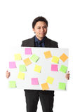 Businessman in grey suit with board full of notes Royalty Free Stock Image