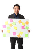 Businessman in grey suit with board full of notes Royalty Free Stock Photos