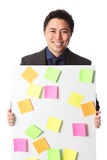 Businessman in grey suit with board full of notes Royalty Free Stock Images