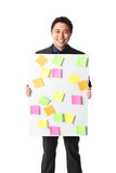 Businessman in grey suit with board full of notes Stock Photos