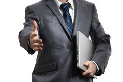 Businessman in grey suit holding laptop in one arm. Businessman in grey suit and a white shirt with a  tie holds laptop and giving a hand  , isolated on a white Stock Photography