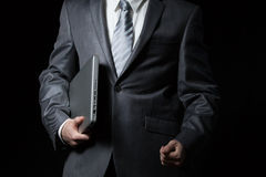 Businessman in grey suit holding laptop in one arm. Businessman in grey suit and a white shirt with a grey tie holding laptop in one arm , isolated on a black Royalty Free Stock Photos