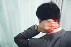Businessman in grey suit neck pain. Stock Photo