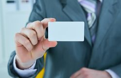 Businessman in grey suit and a pink shirt shows business card with copy space, shallow dept of field. Businessman in grey suit shows business card with copy royalty free stock image