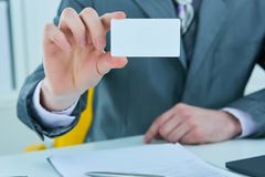 Businessman in grey suit and a pink shirt shows business card with copy space, shallow dept of field. Businessman in grey suit shows business card with copy stock images
