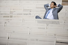 Businessman, in grey suit, sitting in empty stadium seat, hands behind head, eyes closed, smiling stock photos