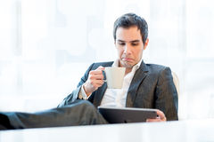 Businessman grimacing in disgust at his tablet Stock Images