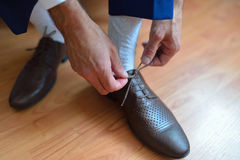 Businessman or groom tie a shoelace on his brown shoes. Shallow depth of field Stock Images