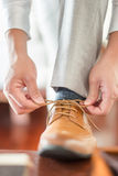 Businessman or groom tied a shoelace on his brown shoes. Stock Image