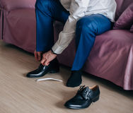 Businessman or groom wears shoes. Businessman or groom wears black shoes blue plants Royalty Free Stock Photos