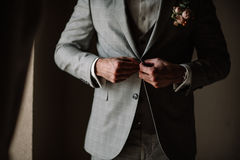 Businessman or groom in white shirt with minty tie fasten button of his blue tweed jacket.  Royalty Free Stock Photo