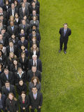 Businessman By Group Of Executives In Row. Businessman standing next to large group of multiethnic businesspeople in row stock photo
