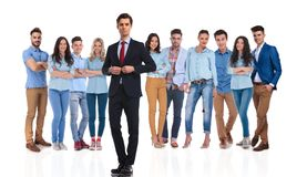 Businessman group leader buttoning suit in front of his team. Businessman group leader buttoning suit jacket in front of his casual team while standing on white royalty free stock images