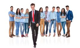 Businessman group leader walking forward in front of his team. Smiling businessman group leader walking forward in front of his casual team while they are stock photo