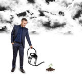 Businessman growing below black clouds Royalty Free Stock Photography