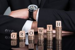 Businessman With Growth Blocks On Stacked Coins Royalty Free Stock Photo