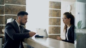 Businessman guest talking with receptionist girl standing at desk in hotel reception and paying bill with credit card. Businessman guest talking with stock video footage