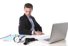 Businessman with gun and alarm clock in deadline, pressure and timing projects concept. Young attractive businessman at office computer desk posing with gun and royalty free stock photos