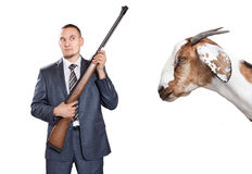 Businessman with gun looking at goat Royalty Free Stock Image