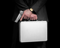 Businessman with gun and silver metal briefcase. Royalty Free Stock Images