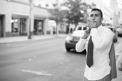 Businessman hailing a taxi cab Stock Photos