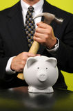 Businessman with Hammer in Front of Piggy Bank Royalty Free Stock Image