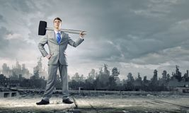 Businessman with hammer Royalty Free Stock Image