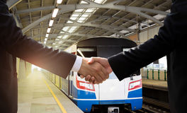 Businessman han dshake agreement with public transport sky train. In background stock images