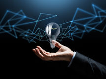 Businessman hand with bulb over dark background Royalty Free Stock Photo