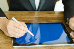 Businessman Hand. Business concept, A businessman used a pen pointer to graph on tablet Stock Photos