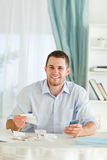 Businessman with hand calculator checking invoices Stock Photo