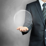 Businessman hand carrying empty transparent ball or globe Royalty Free Stock Photo