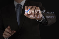 Businessman hand checking  passive or acctive income Stock Image