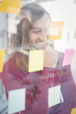 Businessman with hand on chin looking at sticky notes Royalty Free Stock Photo