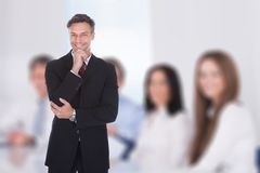Businessman with hand on chin standing in boardroom Stock Image