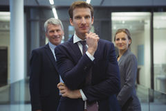 Businessman with hand on chin standing in the office. Portrait of businessman with hand on chin standing in the office Stock Photo