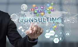 Businessman hand chooses Consulting wording on interface screen. Internet technology service concept royalty free stock photography