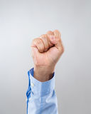 Businessman hand with clench fist. With gray background stock image