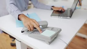 Businessman hand dialing phone number at office