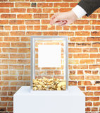 Businessman hand donating money. Businessman hand putting coin into donation box with blank label. Red brick wall background. Charity concept. Mock up, 3D Stock Photography