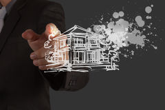 Businessman hand draw house. And splashing color as cocnept stock photography