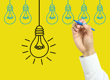Businessman hand drawing bulbs Royalty Free Stock Images