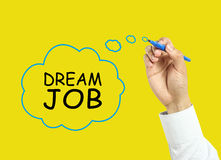 Businessman hand drawing dream job concept. Businessman is drawing dream job concept with marker on transparent board with yellow background Stock Images