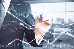 Economy and money concept. Businessman hand drawing forex chart in blurry office interior. Economy and money concept. Double exposure Royalty Free Stock Photo