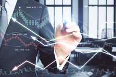 Economy and trade concept. Businessman hand drawing forex chart in blurry office interior. Economy and trade concept. Double exposure Royalty Free Stock Images