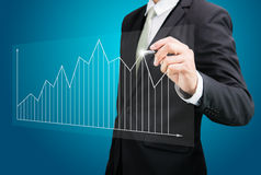 Businessman hand drawing a graph  Stock Images