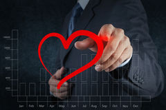 Businessman hand drawing a heart as love concept Royalty Free Stock Image