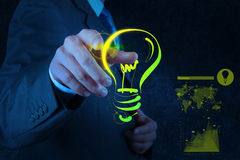 Businessman hand drawing light bulb on touch scree. N computer as success concept stock photo